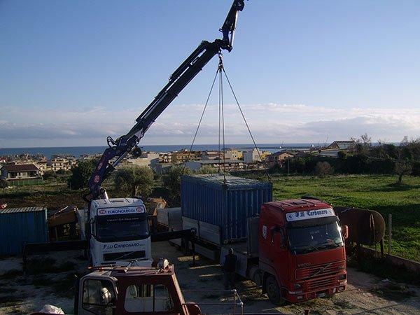 un camion con un braccio meccanico che solleva un container rimorchio di un altro camion