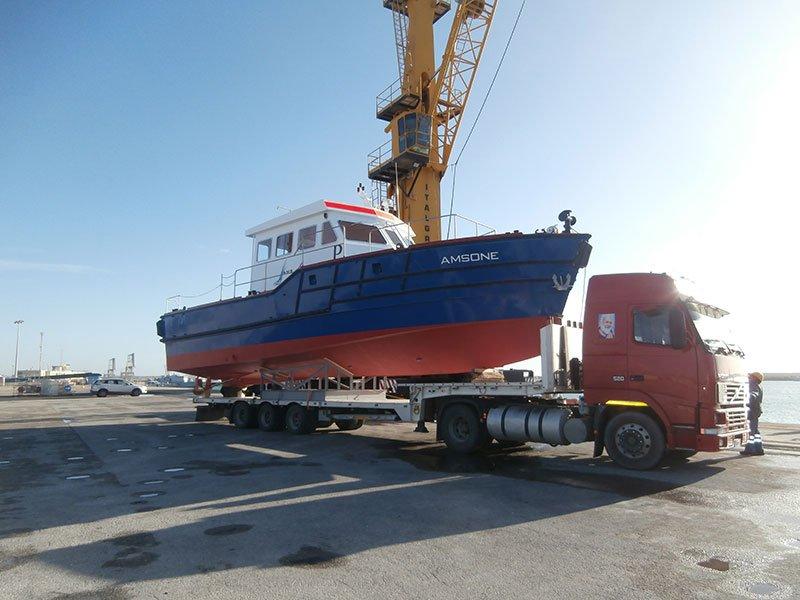 un camion rosso con una barca sul rimorchio