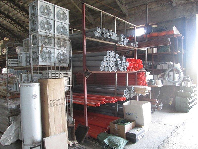 uno scaffale di metallo di color rosso con dei tubi in  ferro di diversi colori in un magazzino