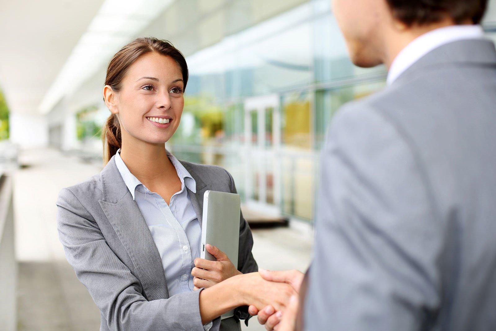 Donna sorridente stringendo la mano di un uomo