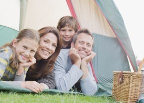 Family of four laid on grass looking out of tent, next to picnic basket