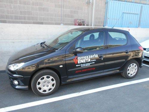 una macchina Peugeot 206 di color nero con scritto Carrozzeria Veneta sulla portiera