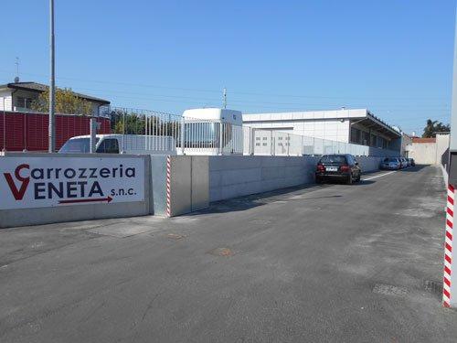 in strada, vista di un cartello con scritto Carrozzeria Veneta e una freccia a destra