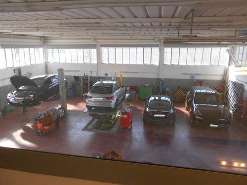 delle macchine su dei ponti all'interno di una carrozzeria viste dall'alto