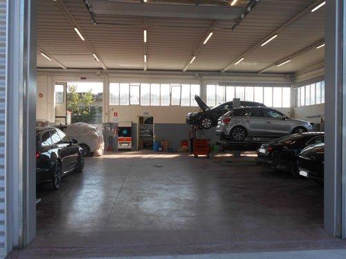 vista dell'interno della carrozzeria con delle macchine sui ponti e parcheggiate