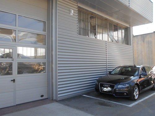 esterno dello stabile con una macchina della marca Audi di color grigio scuro parcheggiata