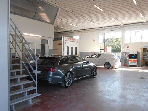 vista dal dietro di una macchina grigia della marca Audi e sulla sinistra una scala in ferro