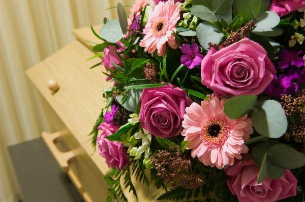 Corona di fiori in tonalità rosa su bara in legno chiaro