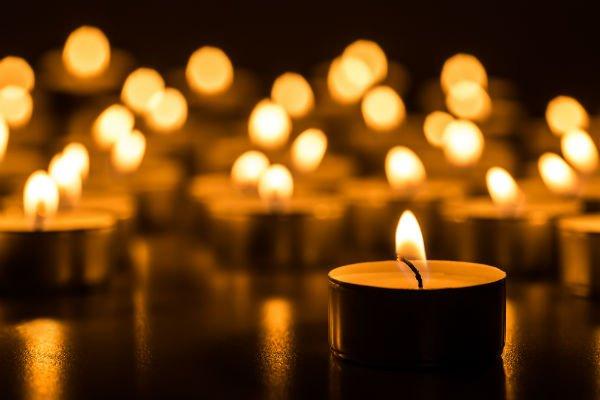 Una candela accesa, molte candele dietro sfocate