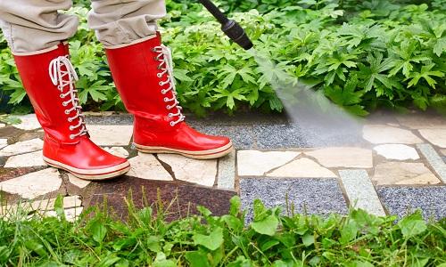 due gambe con degli stivali rossi che usano un idropulitrice