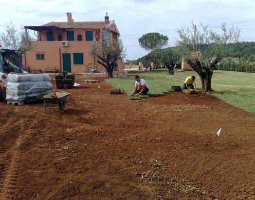 dei giardinieri in un terreno mentre installano un impianto di irrigazioni