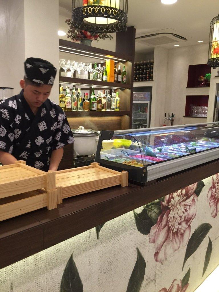 un cuoco in uniforme dietro a un banco di un ristorante