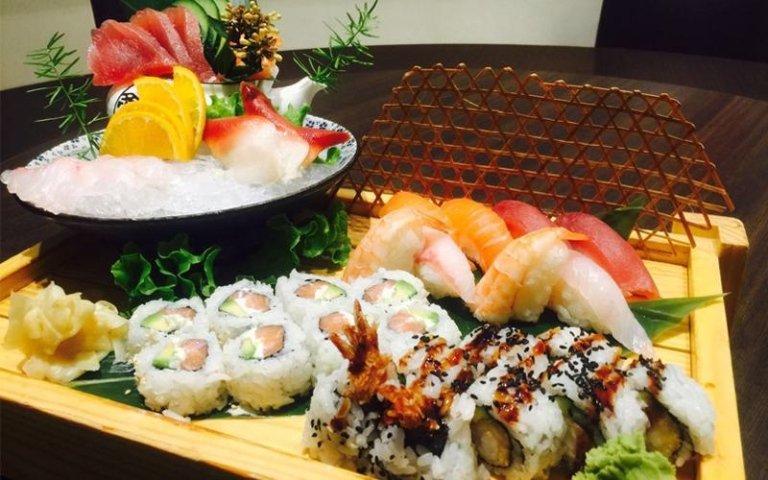 una ciotola con del ghiaccio, carpaccio di pesce e accanto del sushi