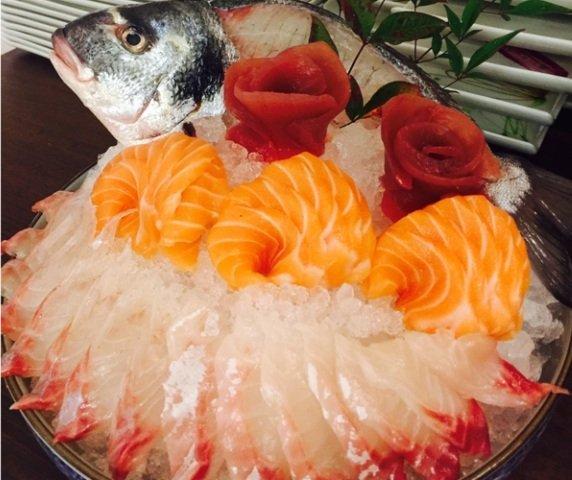 una ciotola con del ghiaccio, carpaccio di salmone, tonno e altro