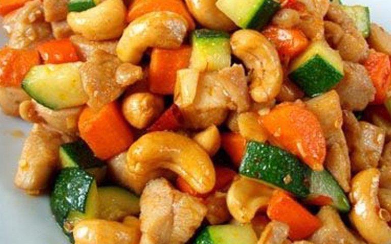 un piatto a base di verdura, carne e degli anacardi