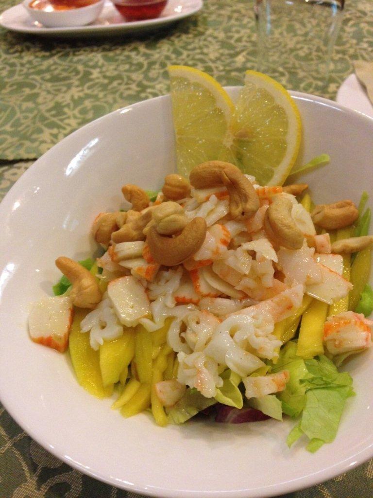 un piatto con frutta, insalata , surimi e degli anacardi tostati