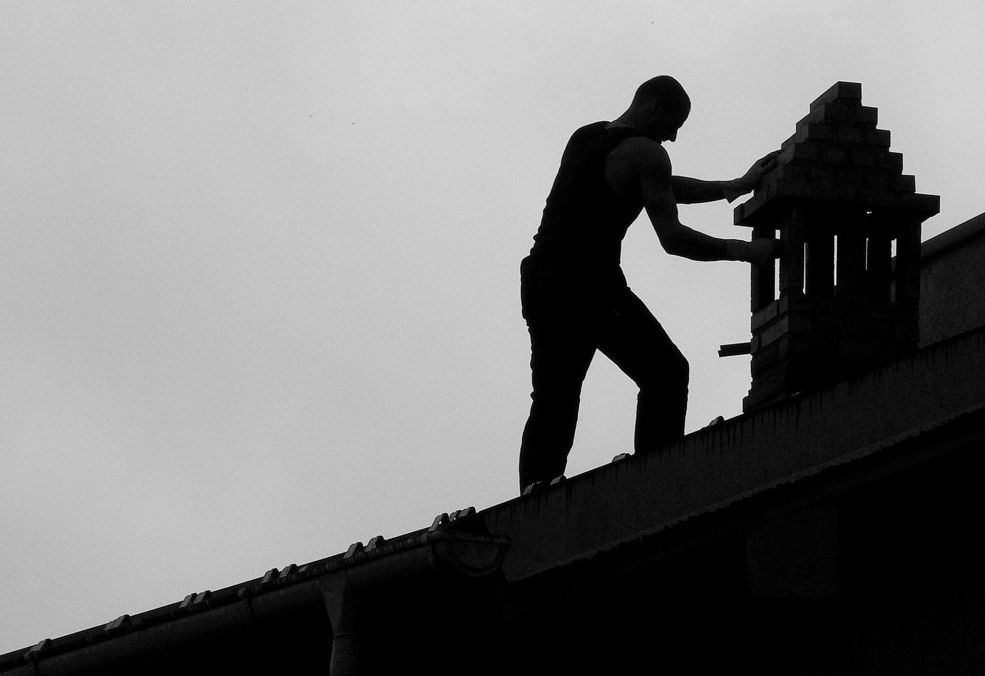 un uomo mentre pulisce una canna fumaria