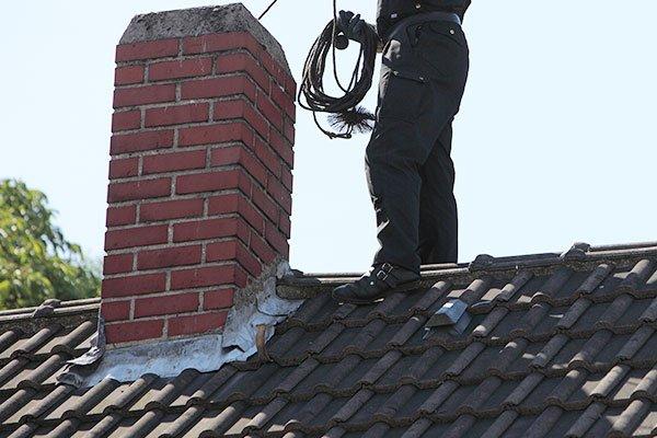 un uomo su un tetto accanto una canna fumaria