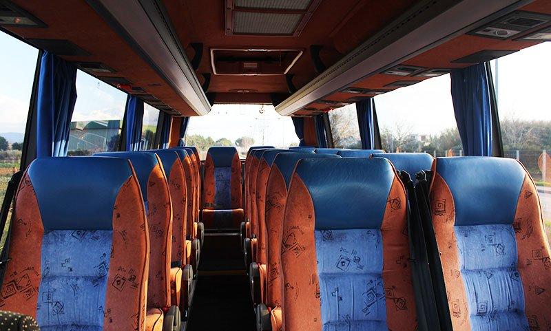 interno di un pullmino con sedile arancioni e blu