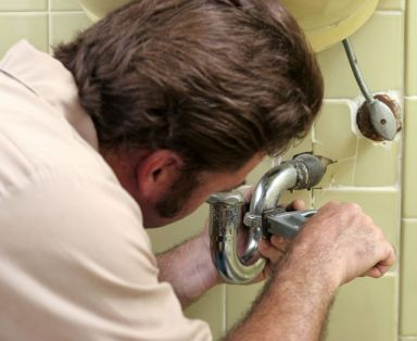 One of the plumbers servicing a tap in Kaitaia