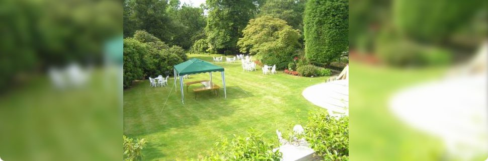 A gazebo in a large landscaped garden