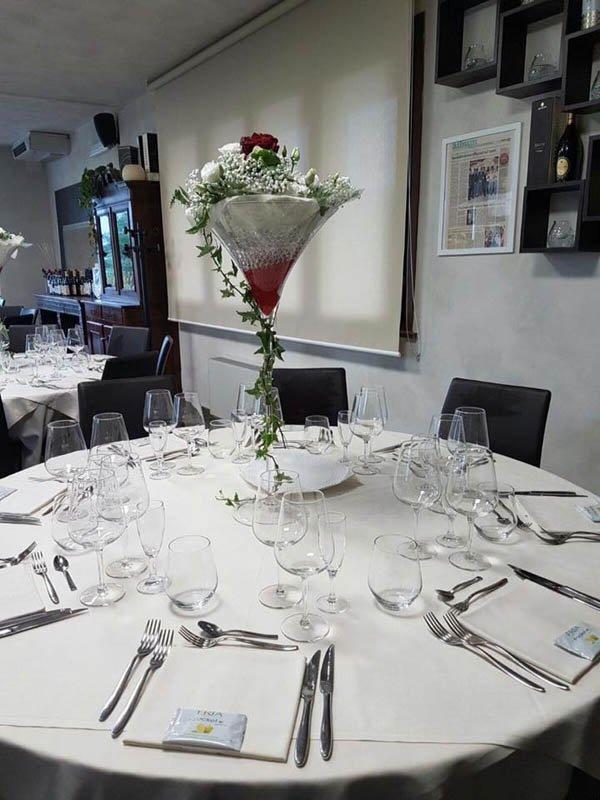 tavolo tondo di ristorante con centrotavola di fiori
