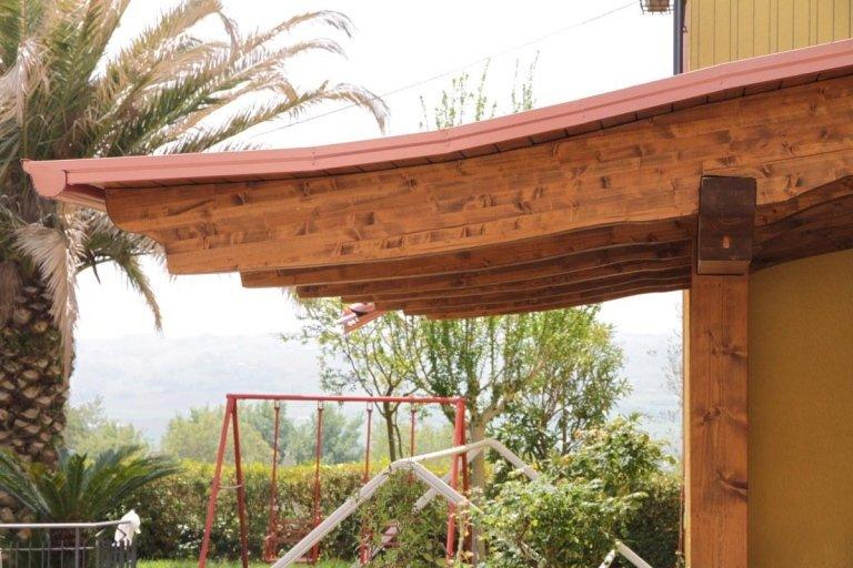 una tettoia in legno e un'altalena in un giardino