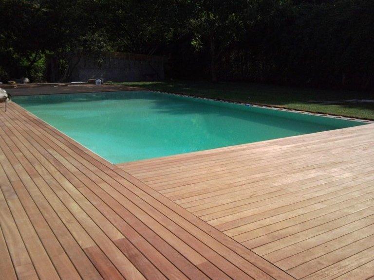 una piscina e attorno una pavimentazione in legno