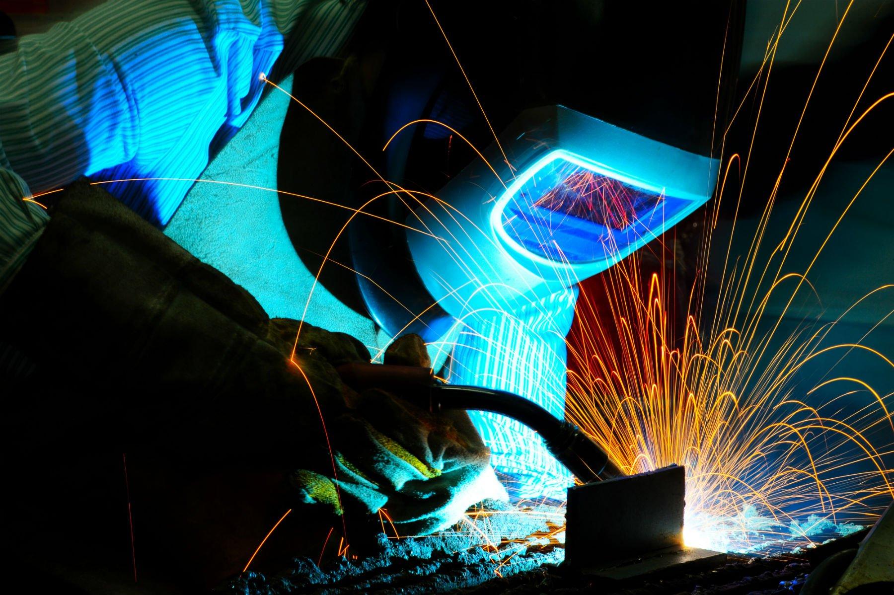 un uomo con un casco di saldatura e mentre lavora con ferro