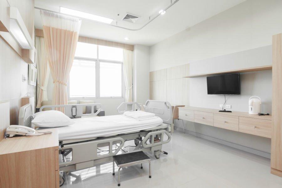 una stanza d' ospedale con un letto, una Tv e due comodini