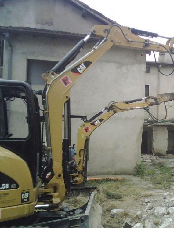 Demolizione edificio con escavatore cingolato e pinza frantumatrice