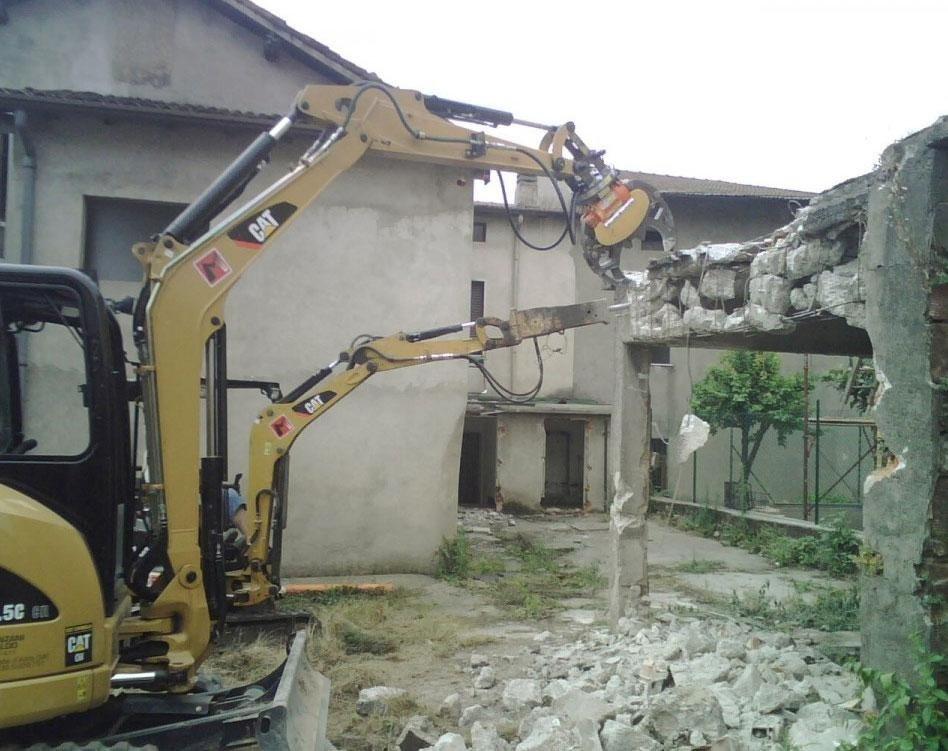 Demolizione edificio con pinza frantumatrice e martello demolitore montati su escavatori