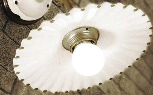 una lampadina accesa di un lampadario bianco