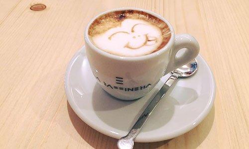 una tazza di cappuccino con delle decorazioni di cacao e accanto un piattino con una brioche