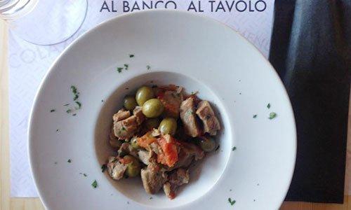 Un piatto a base di carne, olive verdi e pomodori