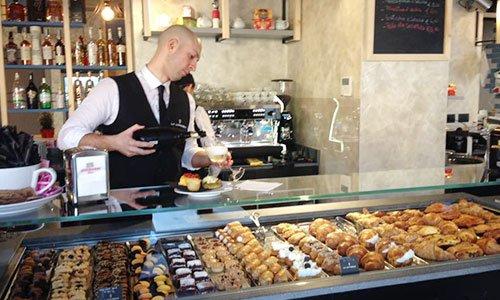 Vetrina con pasticcini e dolci e dietro un barista mentre versa vino bianco dentro un bicchiere