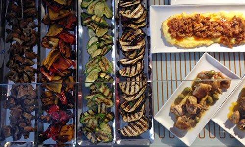 funghi,peperoni rossi e gialli,zucchine e melanzane, il tutto grigliato e messo in un contenitore con degli scompartimenti che dividono ogni prodotto e accanto altre specialità