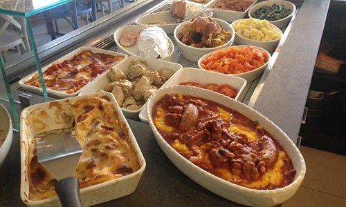 dei recipienti con lasagne, polenta e salsicce, involtini,carote e altre specialità esposte