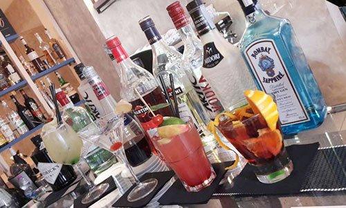 una serie di bottiglie di liquori esposti e bicchieri con dei cocktail