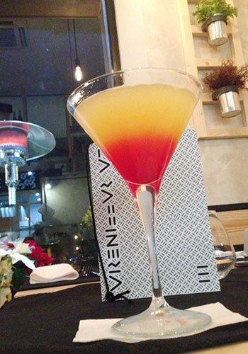 un bicchiere con un cocktail arancione e rosso appoggiato su un tavolo e dietro un menù