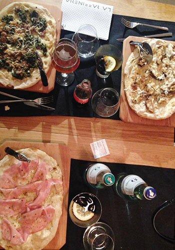 vista dall'alto di un piatto di pizza bianca al prosciutto, e di fronte altre due pizze bianche alle verdure con dei bicchieri, bottiglia di acqua minerale e cocktail dentro ai bicchieri