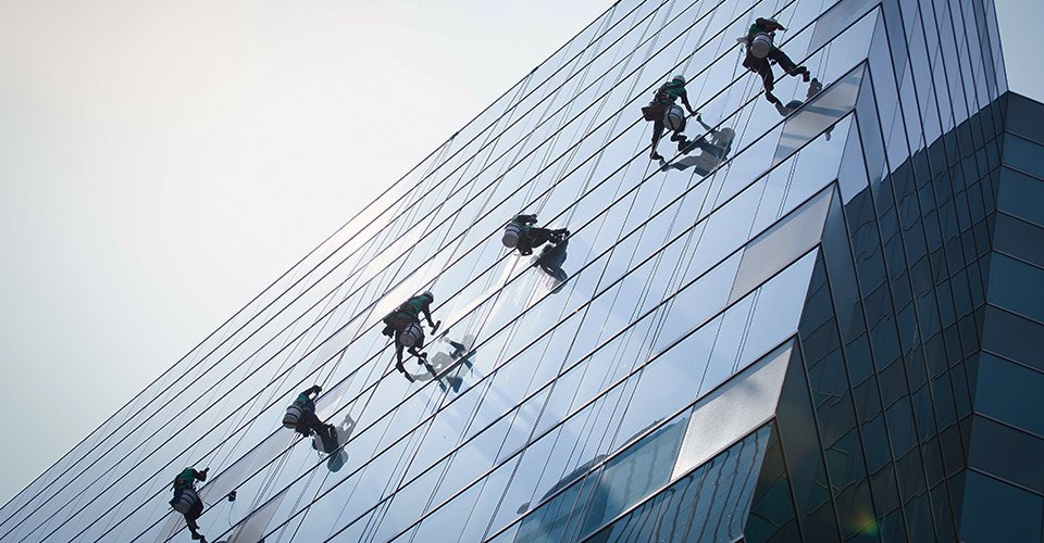set of experts cleaning a high rise building