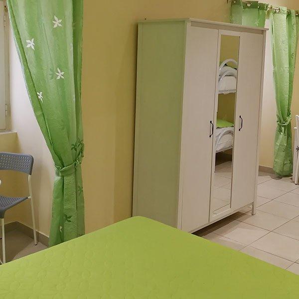 una camera con delle tende di color verde e un armadio con uno specchio