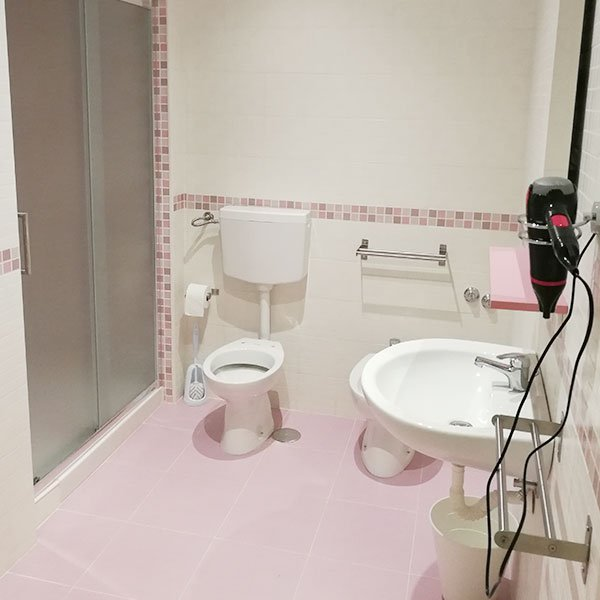 un bagno con un box doccia con delle piastrelle di color rosa