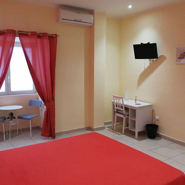 una camera con un letto , una Tv e una scrivania