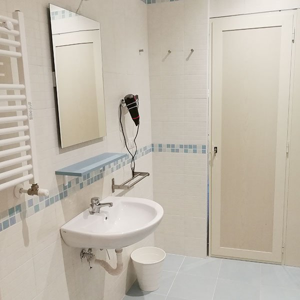 un lavandino con sopra uno specchio al muro