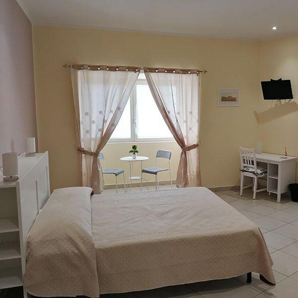 una camera con un letto matrimoniale, un tavolino e una scrivania