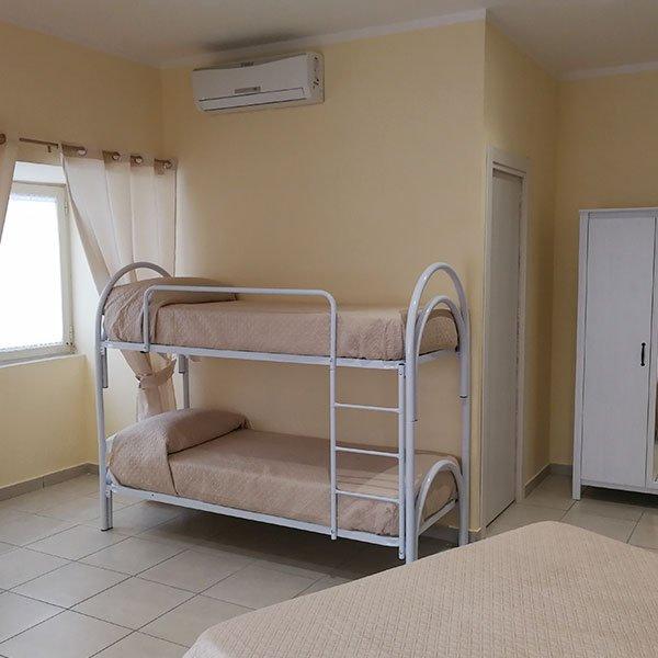 una camera con l'aria condizionata e un letto a castello