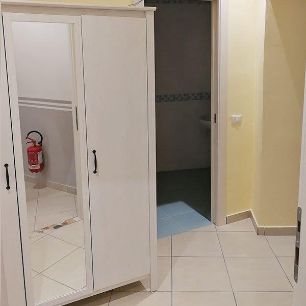 una stanza con un armadio bianco con uno specchio e sulla destra un bagno
