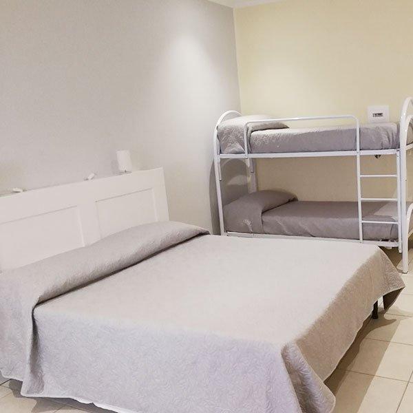 una stanza con un letto matrimoniale e un letto a castello